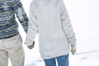 雪原で手をつなぐカップルの後姿