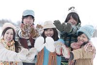 雪のついた手袋を見せる若者たち