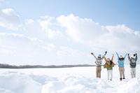 雪原で両手を広げる若者たちの後姿
