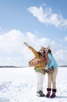 雪原で微笑む2人の女性
