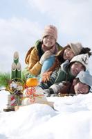 雪原で積み重なる若者たちと正月グッズ
