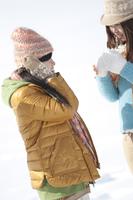 雪原で寒そうにする2人の女性