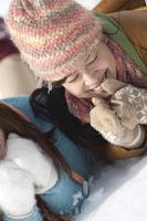 雪原に寝転び微笑む女性