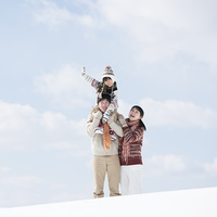雪原で肩車をする家族