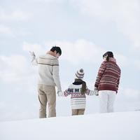 雪原で手をつなぐ家族の後姿
