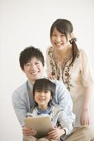タブレットPCを持ち微笑む家族