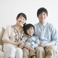 ソファに座り微笑む家族