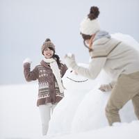雪だるまの周りで雪合戦をするカップル