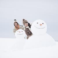 雪だるまの周りで微笑むカップル