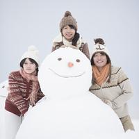雪だるまの周りで微笑む大学生
