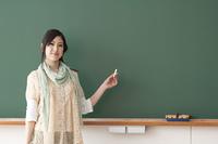 黒板の前で微笑む大学生