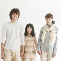 手をつなぎ微笑む家族