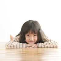 床に寝転び微笑む女の子