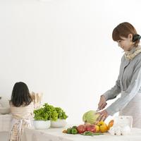 キッチンで料理をする母親と手伝いをする女の子