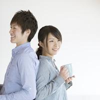 コーヒーカップを持ち微笑むカップル
