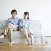 ソファに座り微笑むカップル