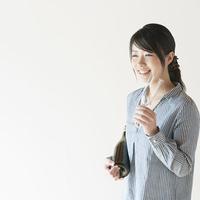 ボトルとシャンパングラスを持ち微笑む女性