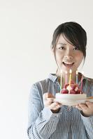 ケーキを持ち微笑む女性