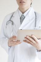 タブレットPCを持つ医者の手元