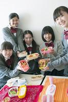 お弁当を持ち微笑む中学生