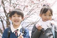 桜の前で微笑む小学生