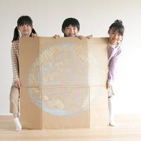 地球の絵を描いた段ボールを持ち微笑む子供たち