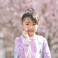 桜の花を持ち頬笑む小学生