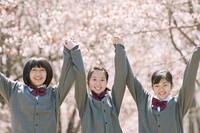 桜の前で手をつなぐ中学生