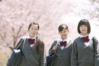 桜の前で微笑む中学生