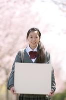 桜の前でメッセージボードを持つ中学生