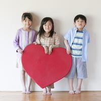 ハートのボードを持ち微笑む子供たち