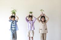 植物を持ち微笑む子供たち