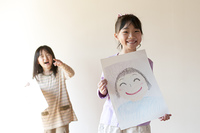 自分の描いた絵を見せる2人の女の子