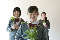 植物を持ち微笑む中学生