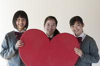 ハートのボードを持ち微笑む中学生