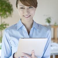 タブレットPCを持ち微笑むビジネスウーマン