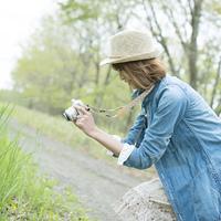 ミラーレス一眼カメラで写真を撮る女性