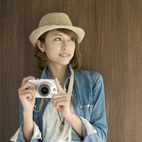 ミラーレス一眼カメラを持ち微笑む女性