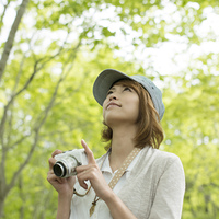 ミラーレス一眼カメラを持ち上を見上げる女性