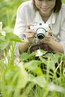 ミラーレス一眼カメラで植物の写真を撮る女性