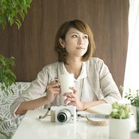 コーヒーカップを持ち窓の外を眺める女性