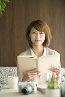 本を持ち微笑む女性