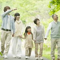 新緑の中で手をつなぐ3世代家族