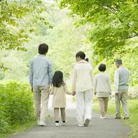 新緑の中で手をつなぐ3世代家族の後姿