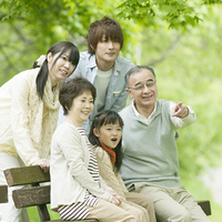 ベンチに座り微笑む3世代家族