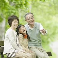 ベンチに座り微笑む祖父母と孫