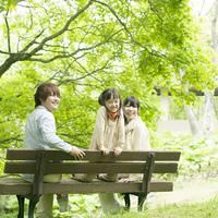 ベンチに座り微笑む家族