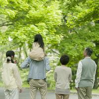 新緑の中に立つ3世代家族の後姿