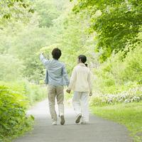 新緑の中を歩くカップルの後姿