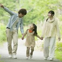 新緑の中で手をつなぐ家族